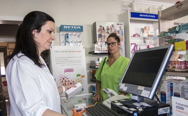 Nerea Matos dispensa los medicamentos a Ana María Periañez, la técnico que luego visita a los domicilios de los mayores./PAKOPÍ
