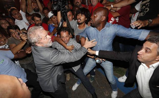 Lula da Silva (c) abandona la sede del Sindicato de los Metalúrgicos de Sao Bernardo do Campo (Brasil) en medio de un tumulto para entregarse a las autoridades. /Sebastião Moreira (Efe)