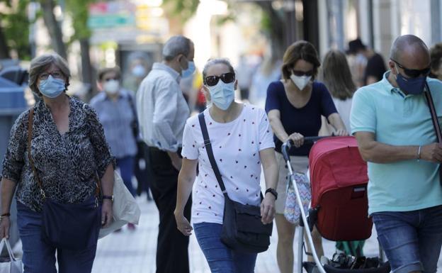 Personas con máscaras en la calle / HOY